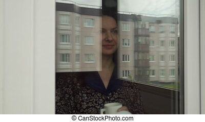 Woman looking out apartment window on cloudy morning happy woman with a cup of coffee