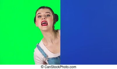 Woman looking out from behind blue blank placard and calls to herself pointing finge on green screen at studio. Girl with two hair-buns and red lips. Copy space. Ready for your text or product, slow motion