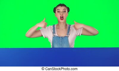 Woman looking out from behind blue blank placard looks at him and nods approvingly, shows like on green screen at studio, slow motion.. Copy space. Ready for your text or product. The board is horizontal