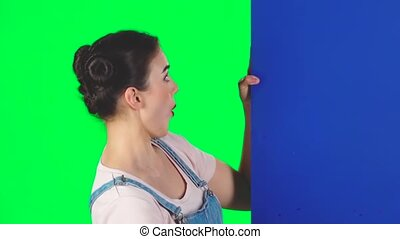 Woman looking out from behind blue blank placard looks at him and nods approvingly on green screen at studio, slow motion.. Girl with two hair-buns, red lips. Copy space. Ready for your text or product