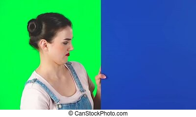 Woman looking out from behind blue blank placard looks at him and shakes his head disapprovingly on green screen at studio, slow motion. Copy space. Ready for your text or product