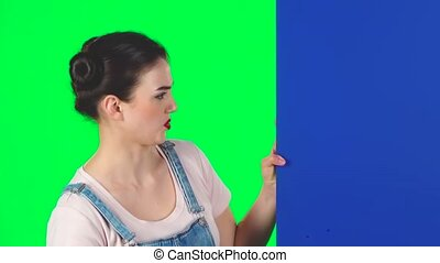Woman looking out from behind blue blank placard looks at him and shakes his head disapprovingly on green screen at studio, slow motion.. Girl with two hair-buns and red lips. Copy space. Ready for your text or product