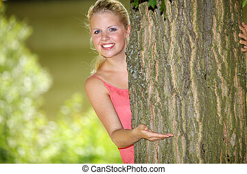 Woman looking out from behind tree