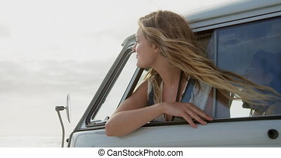 Woman looking out of camper van window 4k - Front view of ...