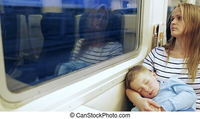 Woman looking out the train window with her son sleeping on the lap