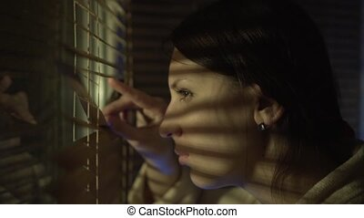 Woman looking out the window through the blinds to the street, spying.