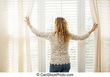 Woman looking out window - Woman looking out big bright...