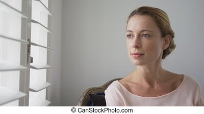 Woman looking outside through window at comfortable home 4k