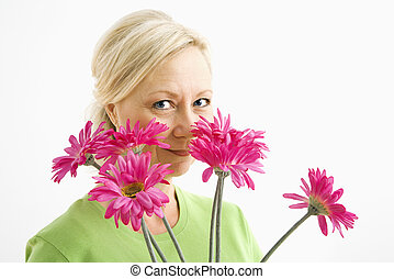 Woman looking over flowers.