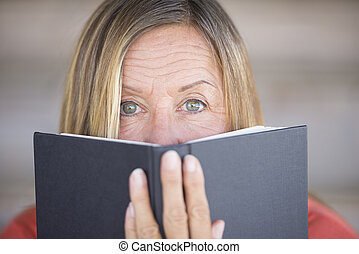Woman looking over reading book cover