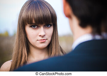 Woman looking seriously over man shoulder
