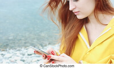 Woman looking something on the phone on the sea coast. -...
