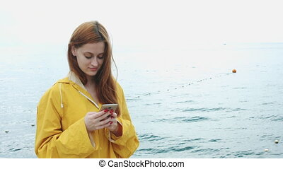 Woman looking something on the phone on the sea coast.