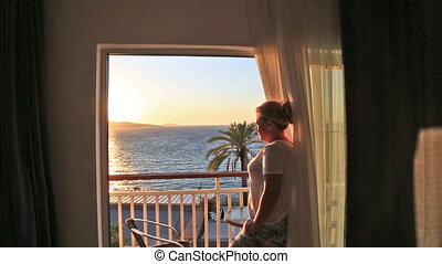 Woman looking the sea from bedroom