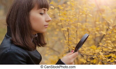 Woman looking through a magnifier on leaves
