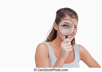 Woman looking through a magnifying glass against a white...