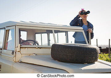 Woman looking through binoculars at countryside