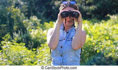 Woman looking through binoculars. Girl tourist with a backpack. outdoor