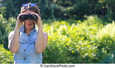 Woman looking through binoculars. Girl tourist with a backpack. outdoor.