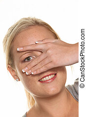 woman looking through fingers of her hand