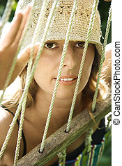 Woman looking through hammock.