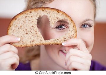 Woman Looking Through Heart Shaped Hole In Bread - Closeup...