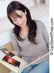 woman looking through photo album