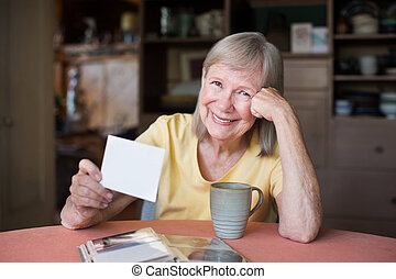 Woman looking through photos in picture album