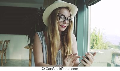 Woman looking through pictures on smartphone in cafe . Beautiful young girl drinking coffee and smiling.