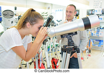 Woman looking through telescope in shop