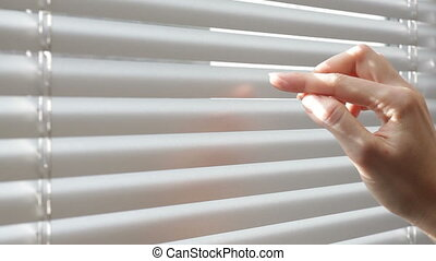 Woman looking through the blinds of the window to the street