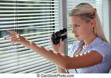 woman looking through the blinds with binoculars