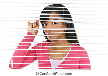 Woman looking through venetian blinds - Young black woman ...