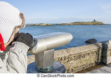 woman looking to Dalkey island by binoculars