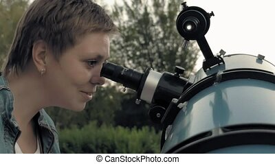 Woman looking to the moon through telescope - Smiling woman...