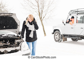 Woman looking under broken car hood snow