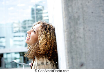 Woman looking up and laughing outdoors