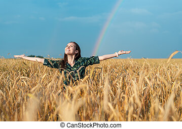 Woman looking up at the sky hands to the side in a field with cereal on a rainbow background