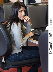 Woman looking up from computer desk in class