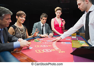 Woman looking up from poker game and smiling