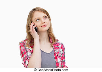 Woman looking up while holding a mobile phone