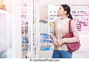 Young woman looking for a medication on the shelves