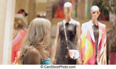 Woman looks admiringly at the windows of boutiques in Milan