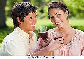 Woman looks ahead while smiling as she is linking arms with her friend and holding glasses of red wine in a park