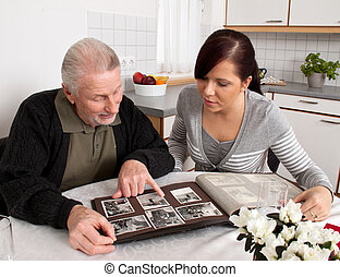 Woman looks at a photo album with seniors