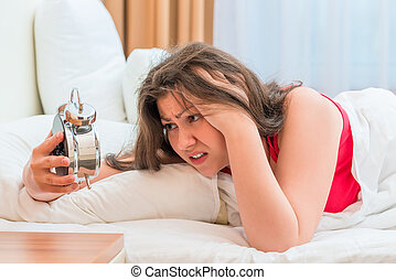 woman looks at an alarm clock, can not to fall asleep