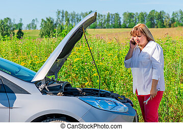 woman looks at engine and speaks on the phone
