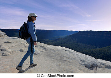 Woman looks at the landscape from Lincoln Rock Lookout at sunset of the Grose Valley located within the Blue Mountains New South Wales Australia