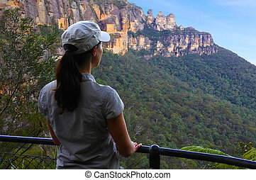 Woman looks at the landscape of The Three Sisters rock formation in the Blue Mountains of New South Wales Australia