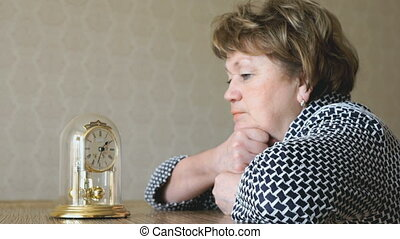 Woman looks at the table clock with pendulum